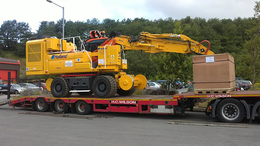 A Doosan 170 on the back of a flatbed, ready for transport